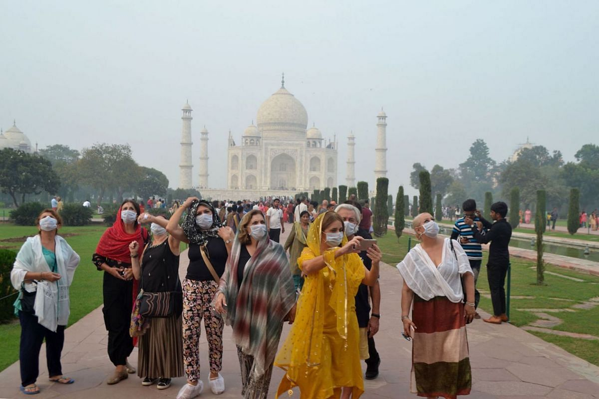 Foreign tourists wearing face masks visit the Taj Mahal under heavy smog conditions, in Agra, India on Nov 4, 2019. As smog levels exceeded those of Beijing by more than three times, authorities also parked a van with an air purifier near the Taj Mah