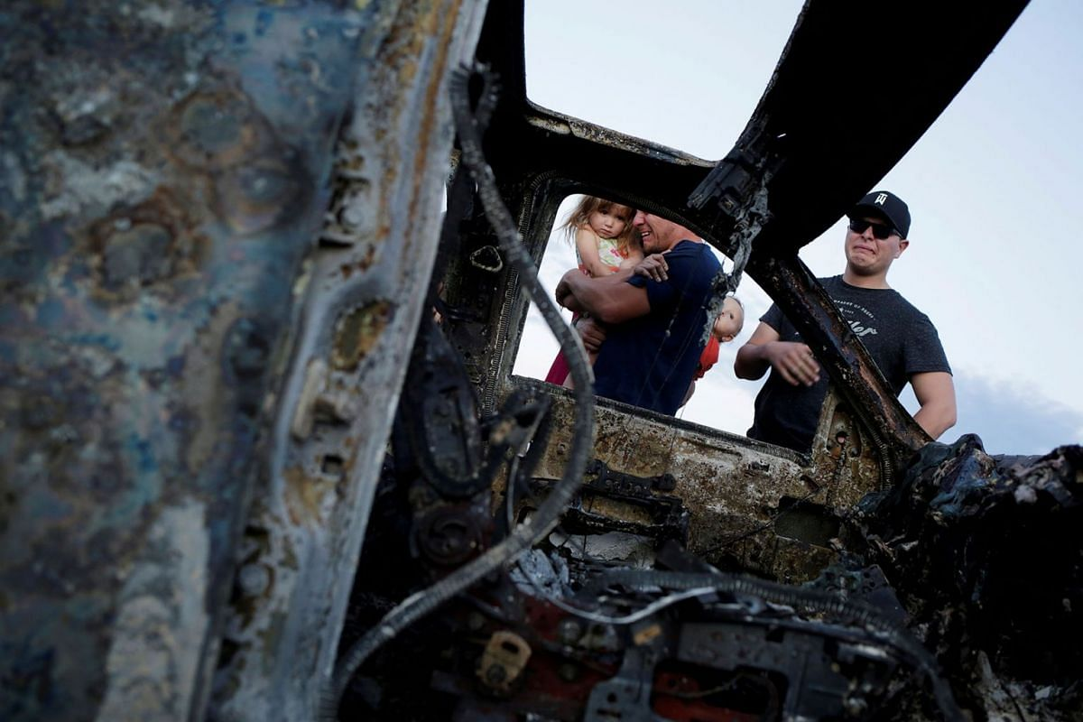 Relatives of slain members of Mexican-American families belonging to Mormon communities react next to the burnt wreckage of a vehicle where some of their relatives died, in Bavispe, Sonora state, Mexico November 5, 2019. PHOTO: REUTERS