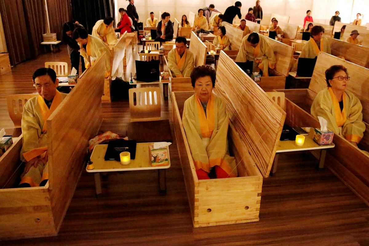 """A photo issued on Nov 7, 2019, shows participants sitting inside coffins during a """"living funeral"""" event as part of a """"dying well"""" programme, in Seoul, South Korea, October 31, 2019. PHOTO: REUTERS"""