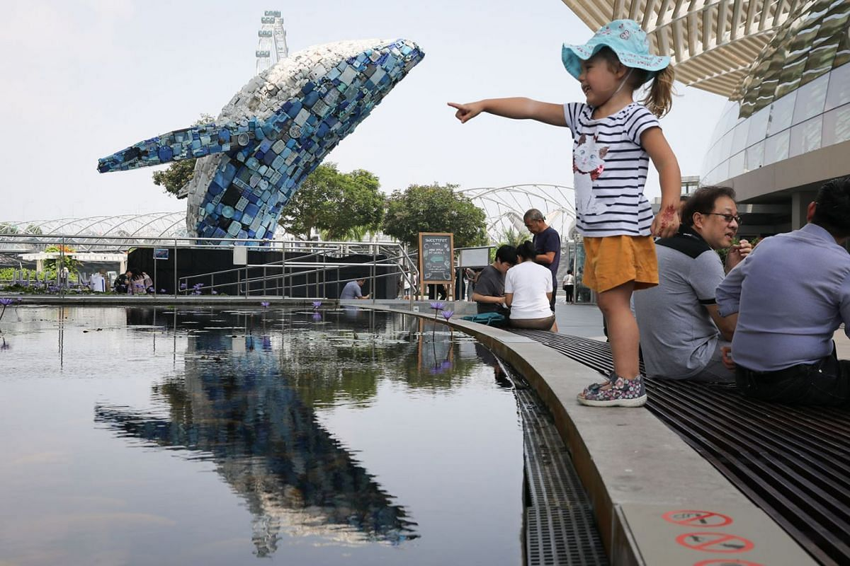 """A girl gestures near """"Skyscraper"""", the Bruges Whale, on Nov 7, 2019 in front of the ArtScience Museum, Singapore. The sculpture of a breaching whale implores observers to consider whether humans have collectively breached the limit of plastic put int"""