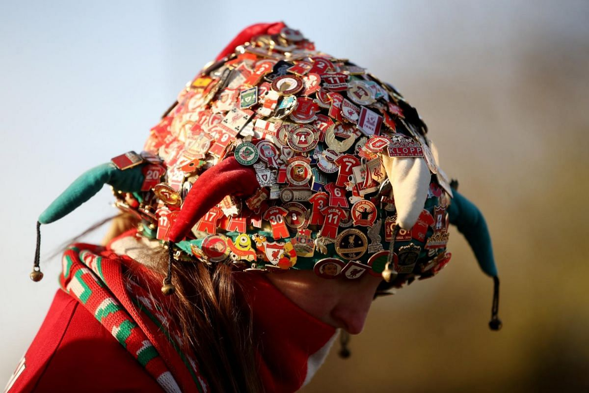 A Liverpool fan with decorated headgear waits outside Anfield stadium before the team's match against Manchester City, on Nov 10, 2019.