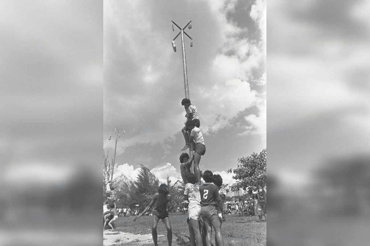 Team members help one another to climb up a slippery betelnut tree trunk during a game in conjunction with the Malay Cultural Fiesta at East Coast Park in 1981.