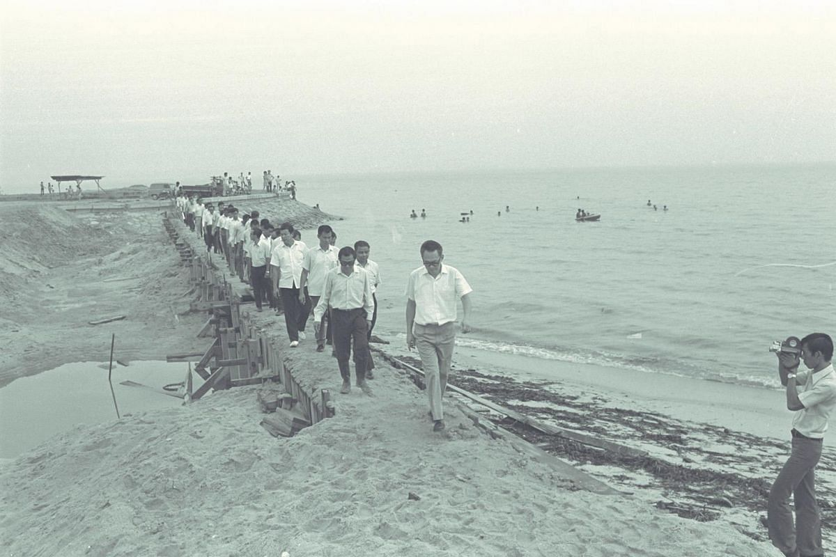 Then Prime Minister Lee Kuan Yew on his way to plant a raintree sapling at the site of the future East Coast Park swimming lagoon in 1972. The lagoon would be completed four years later and be able to accommodate up to 6,000 people.