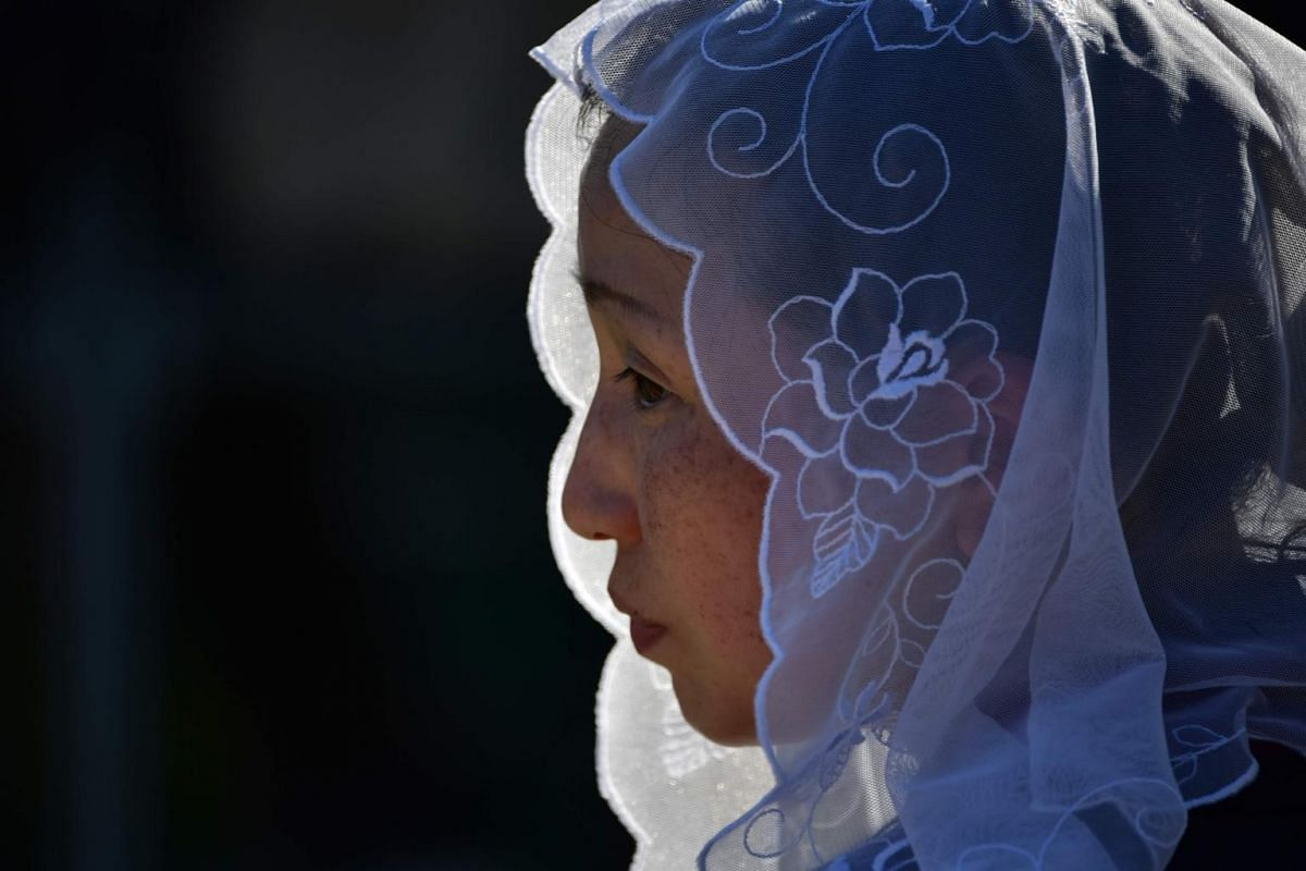 A woman attends a Holy Mass by Pope Francis at a baseball stadium in Nagasaki, on Nov 24, 2019.