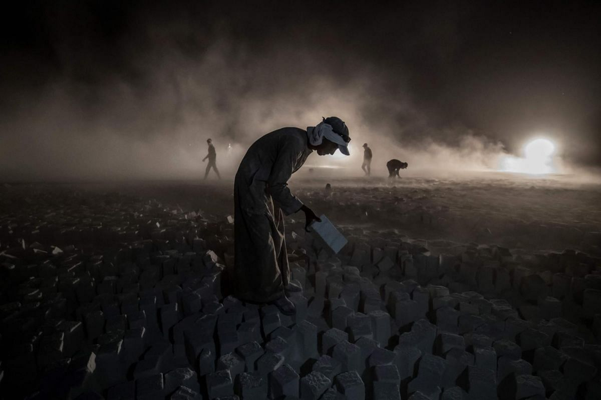 """A labourer carries a stone block while working late at the """"White Mountain"""" limestone extraction quarry site near Egypt's southern city of Minya, some 265km south of the capital, on Nov 13, 2019."""