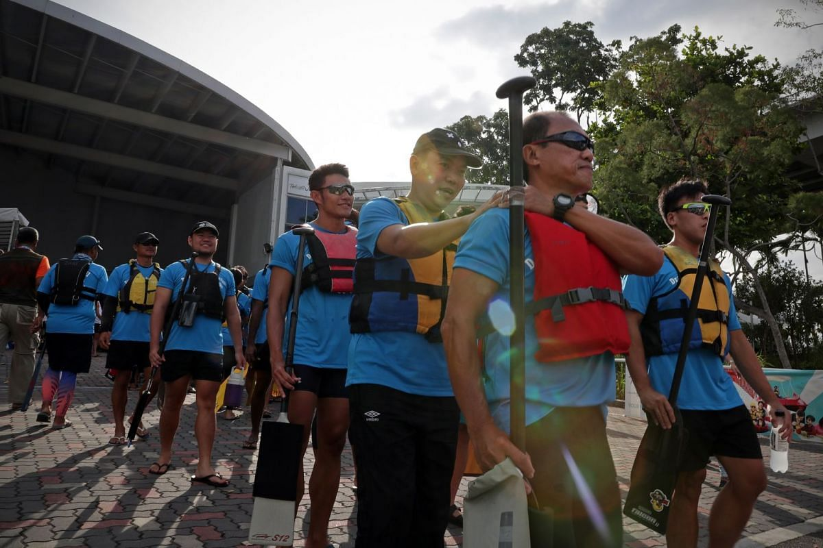 Mr Loo (third from right) being led out to the reporting zone by his buddy Bill Chng (in a red vest), 61, who is a volunteer with DB Hearts and SAVH. Each participant with a disability is partnered with a teammate who is able-bodied. There were more than
