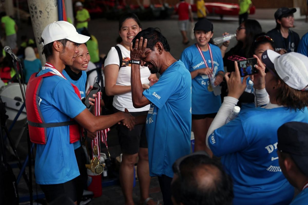Coach Ivan Wong (in a white cap), 32, presenting the first-place medal to visually impaired participant Mahendran Pasupathy. At 73, he was the oldest participant in the dragon boat team from SAVH competing in the event.