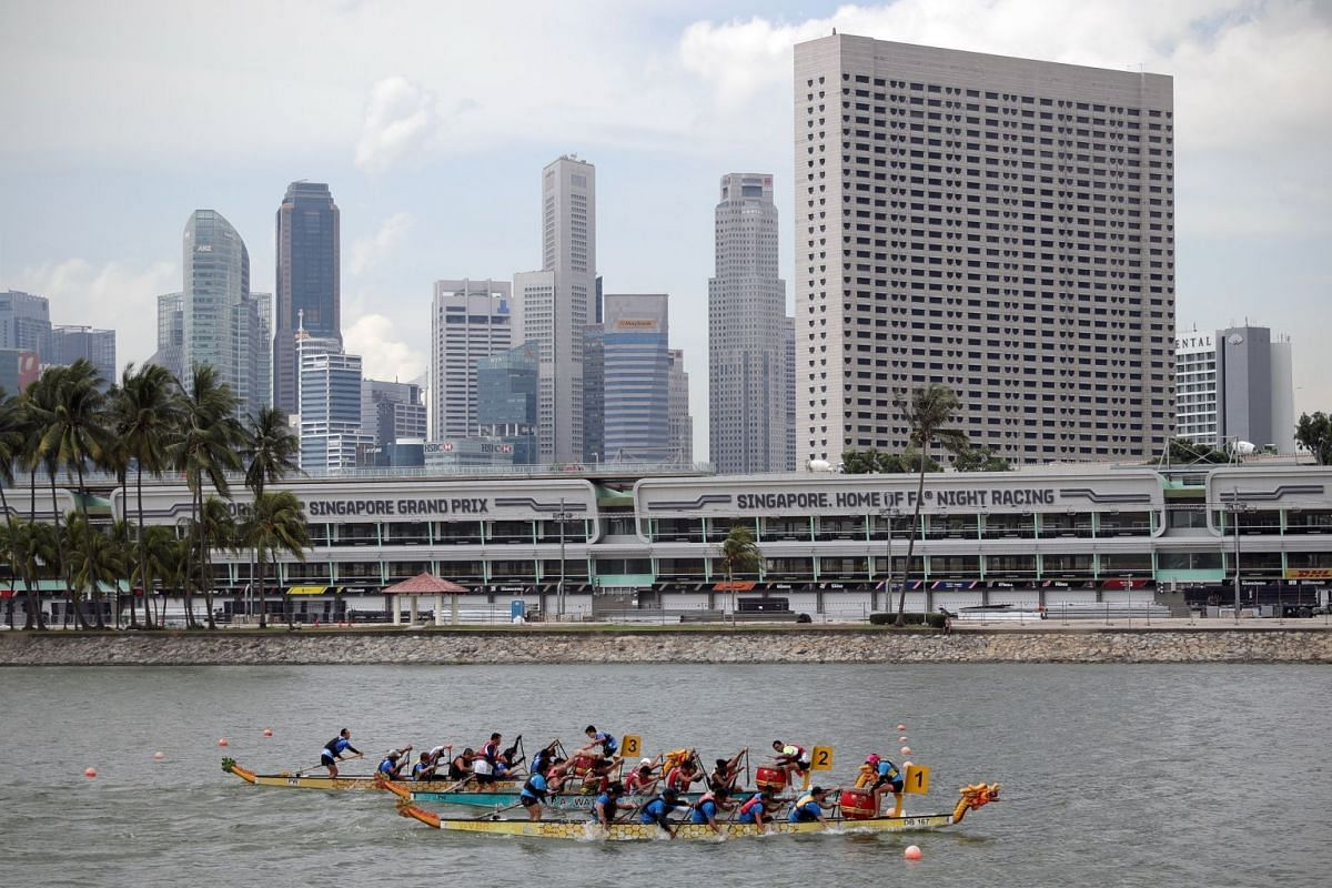 """Mr Loo (second from right, in a yellow vest) competing with Team DragonSail GoGoGo (Boat #1) in the """"DB12 Inter-generation Open"""" race, which they won with a timing of 59.16sec, beating Team Kraken from Punggol Coast Community Sports Club (Boat #2) and Tea"""