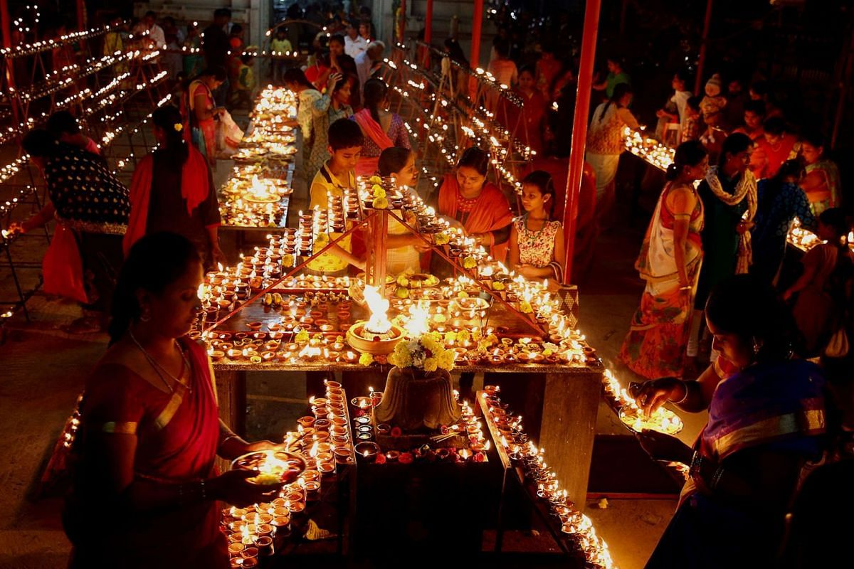 Indian Hindu devotees light earthen lamps and oil lamps in and around the sacred temple of the Shiva temple, during the 'Laksha Deepotsava' celebrations held as part of the 'Karthika Masa' puja in Bangalore, India, November 25, 2019.