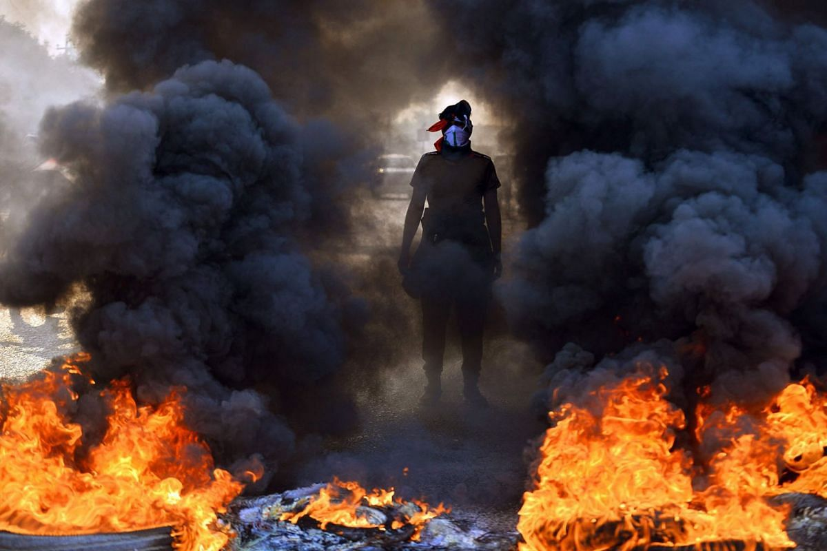 An Iraqi protester stands before burning tires at a roadblock in the central holy shrine city of Najaf on November 26, 2019. PHOTO: AFP