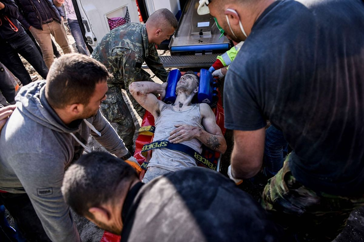 Soldiers and rescue workers carry an injured man found in debris of a collapsed building in Thumane, northwest of capital Tirana, after an earthquake hit Albania, on November 26, 2019. PHOTO: AFP