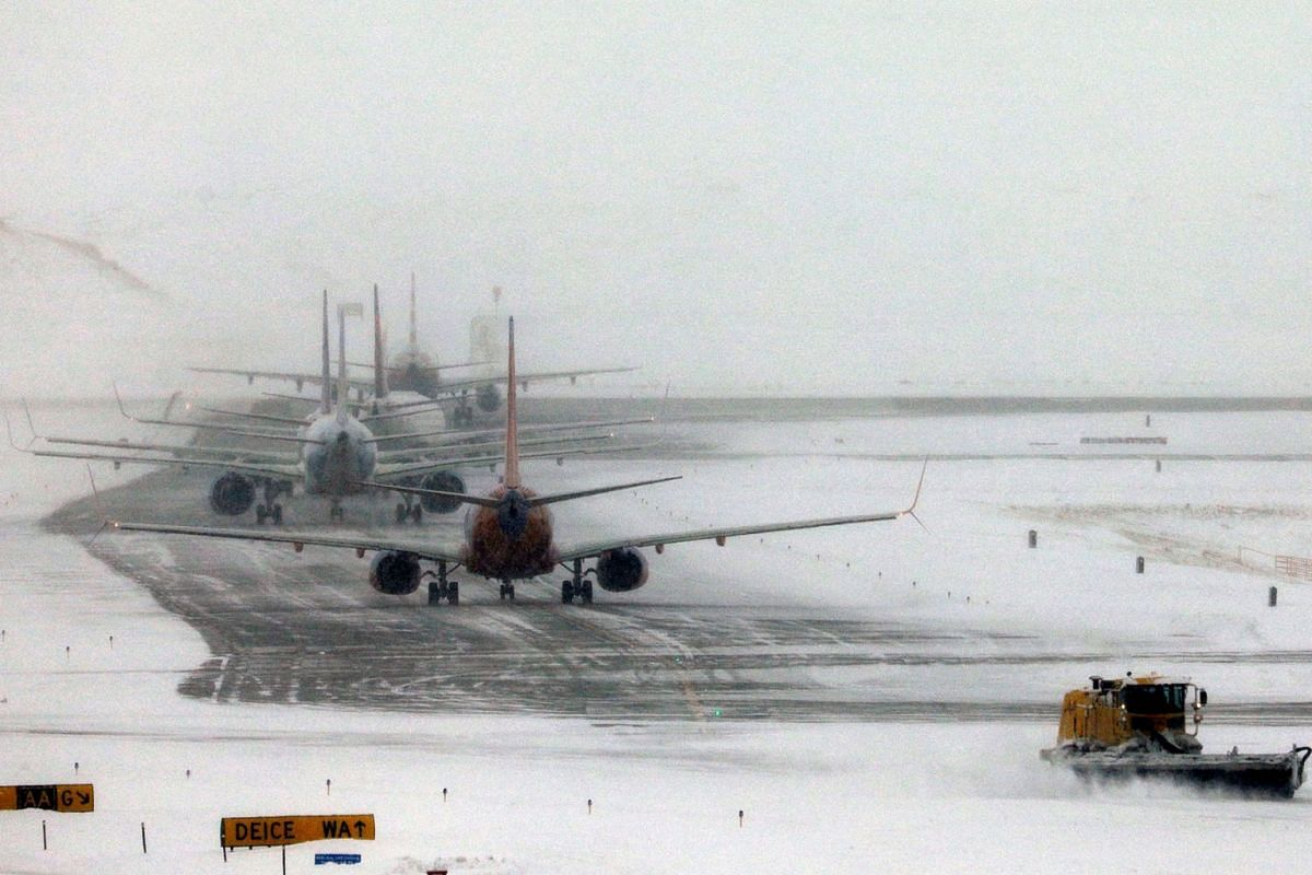 A snowplow clears a runway near a line of jets waiting to takeoff after a pre-Thanksgiving holiday snowstorm caused more than 460 flight cancellations at Denver International Airport, Colorado, U.S., November 26, 2019. PHOTO: REUTERS
