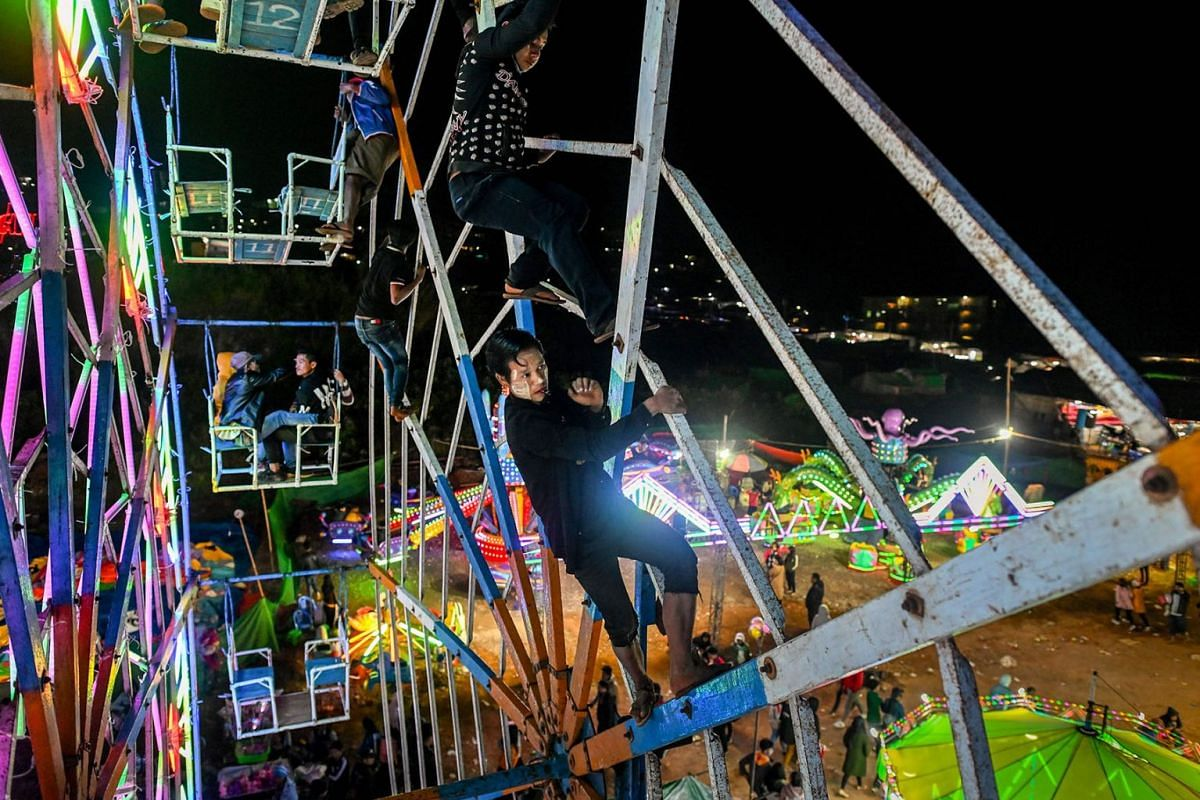 A photo issued on Nov 27, 2019 shows Aung Sein Phyo (C), 22, and other crew members operating a human-powered ferris wheel in Taunggyi, Shan state on Nov 6, 2019 . Myanmar's human-powered big wheels, is reliant on gravity-defying agility and split-se