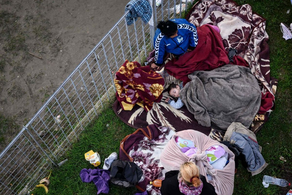 A boy sleeps outdoors at a makeshift camp at a football stadium in Durres, western Albania, on Nov 27, 2019.