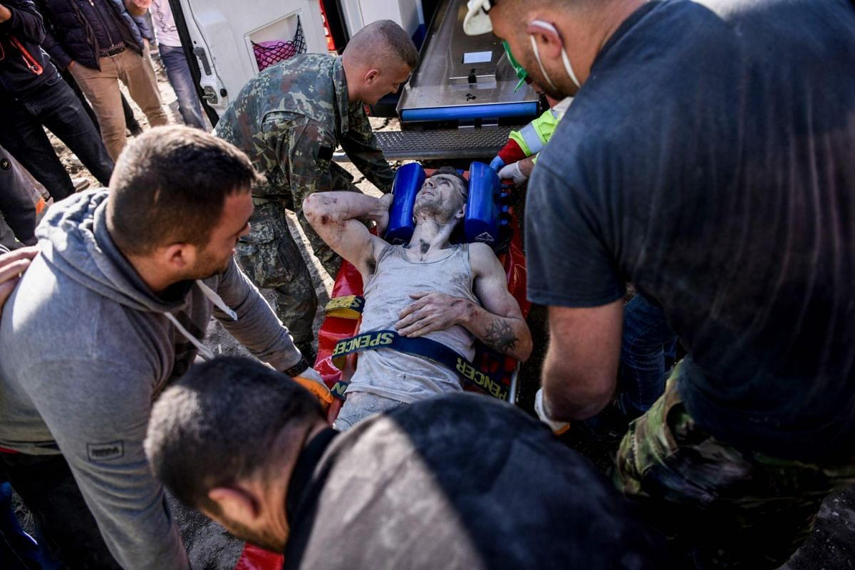Soldiers and rescue workers carry an injured man found in the debris of a collapsed building in Thumane, north-west of capital Tirana.