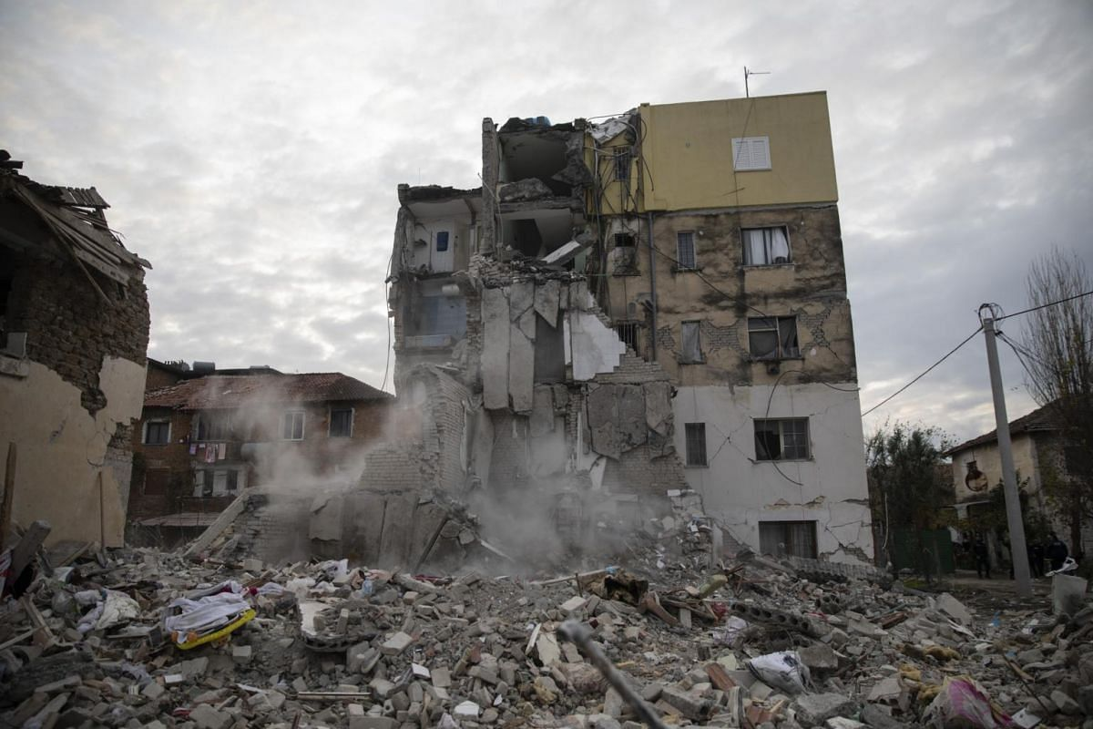 Dust rises from falling parts of a destroyed building during an aftershock in Thumane.