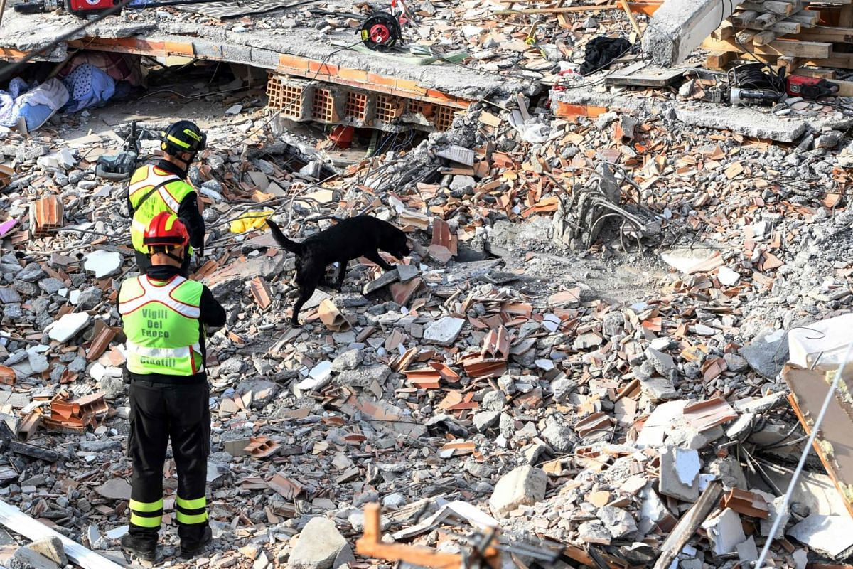 Italian rescuers work with a rescue dog to search for survivors through the rubble of a collapsed building in Thumane, on Nov 27, 2019.