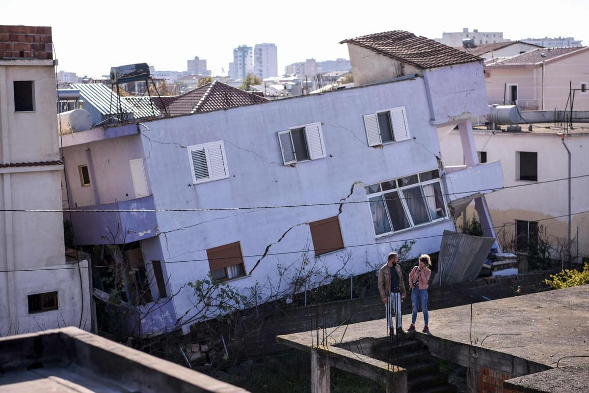 People stand in front of a collapsed building in the town of Durres, western Albania, on Nov 27, 2019.