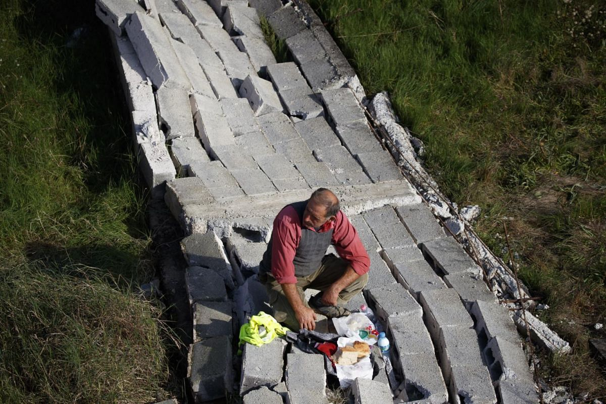 A local man eats his meal on a destroyed section of a wall, on Nov 27, 2019.