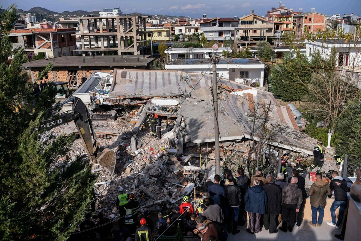 Onlookers gather to watch as Italian search and rescue workers look for survivors stuck under the rubble of a collapsed building in the town of Durres, western Albania on Nov 27, 2019.