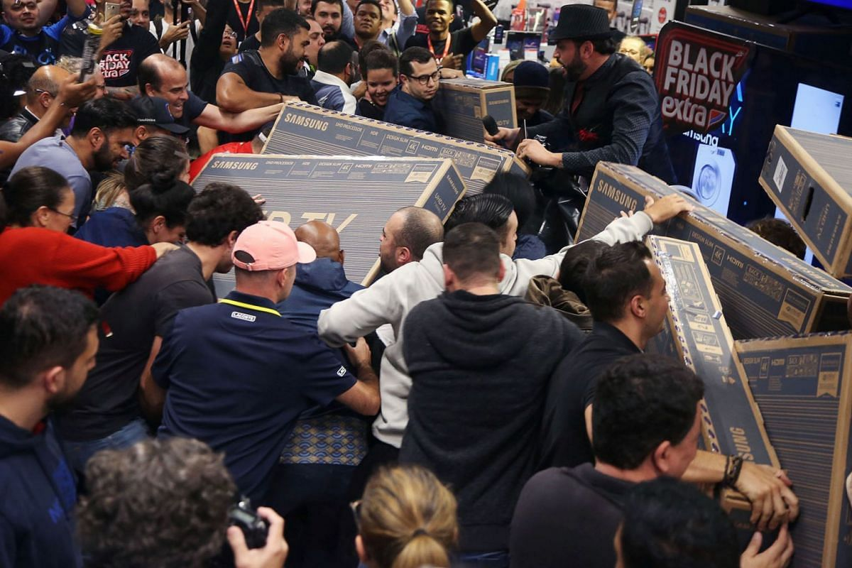 Shoppers reach for television sets as they compete to purchase retail items on Black Friday at a store in Sao Paulo, Brazil, November 28, 2019.  PHOTO: REUTERS
