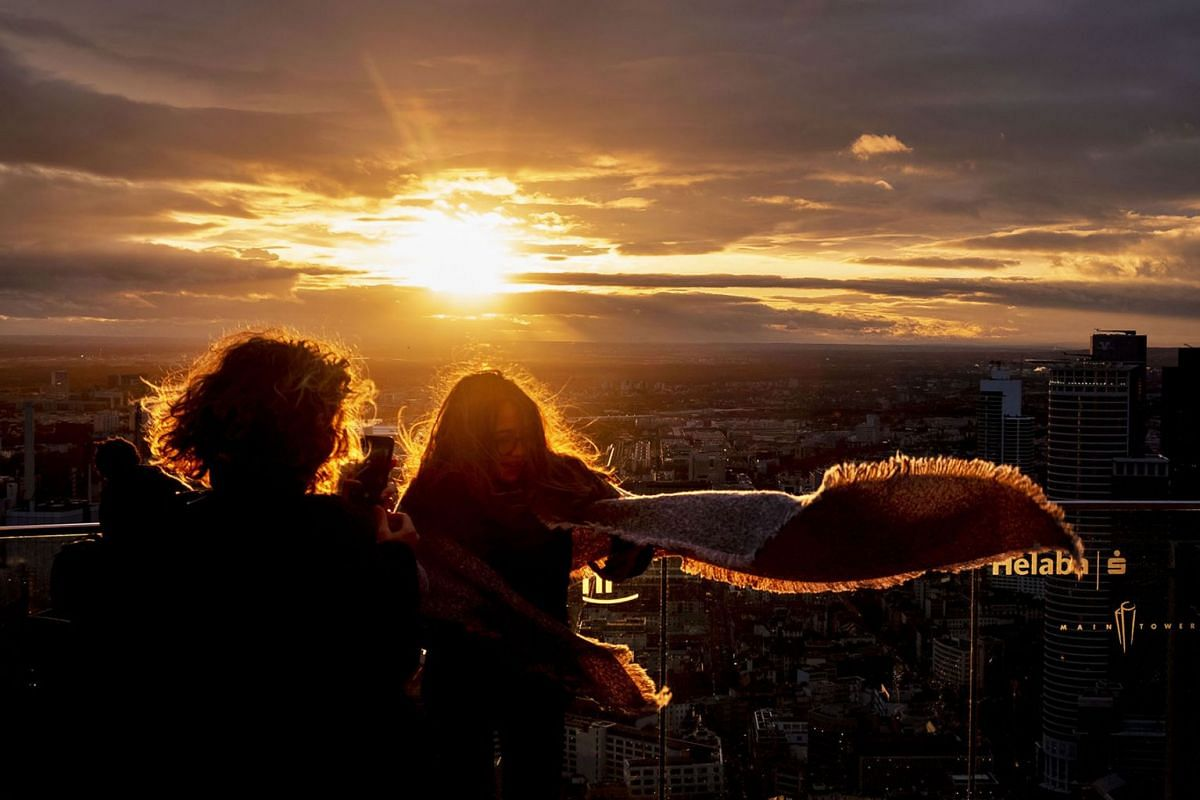 A woman takes a picture of her daughter on the view platform of the Main tower in Frankfurt, Germany, as the sun sets on a stormy Thursday, Nov. 28, 2019. PHOTO: AP