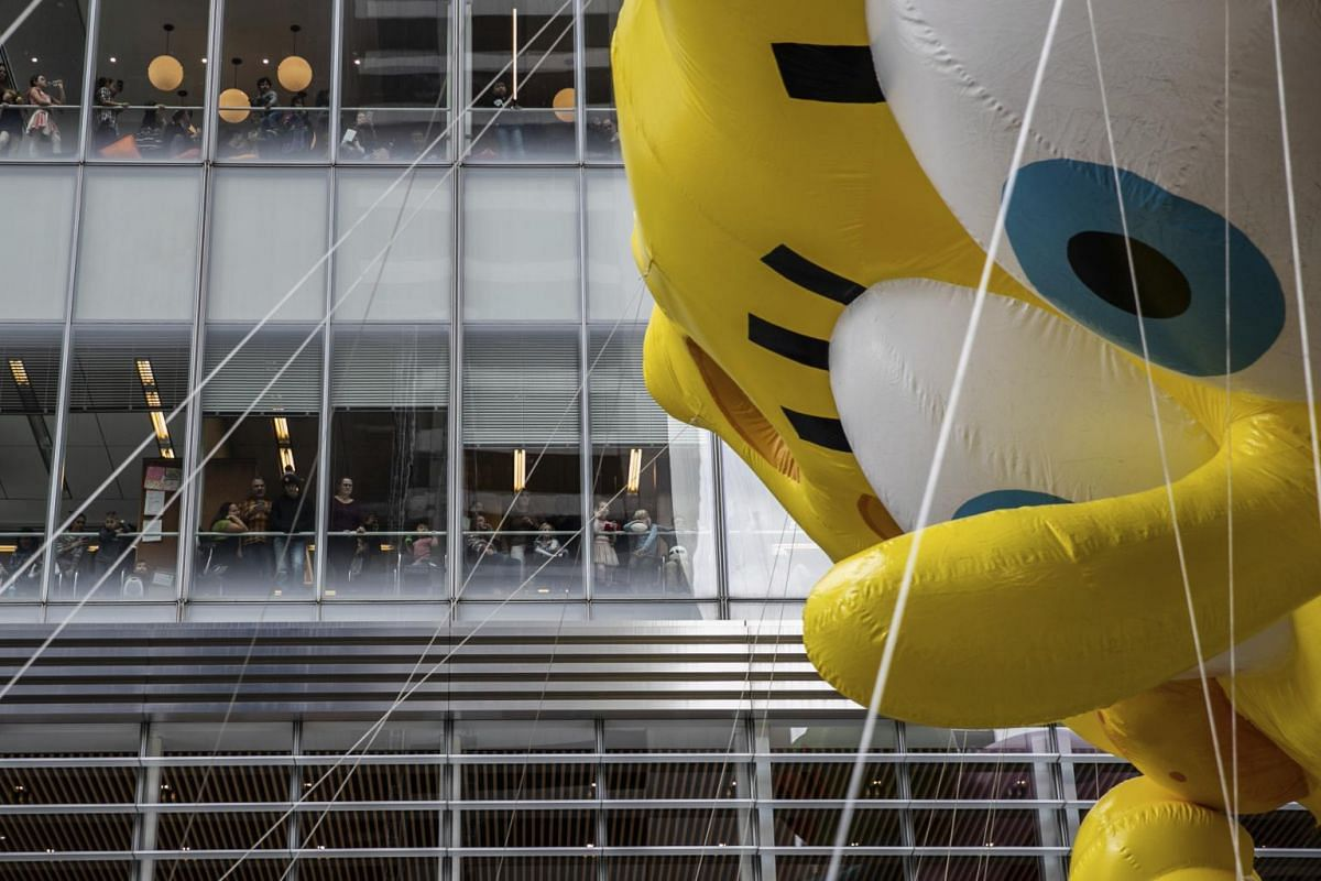 People watch from an office in Sixth Avenue as a Spongebob Squarepants balloon passes by during the Macy's Thanksgiving Day Parade in New York, on Nov 28, 2019.