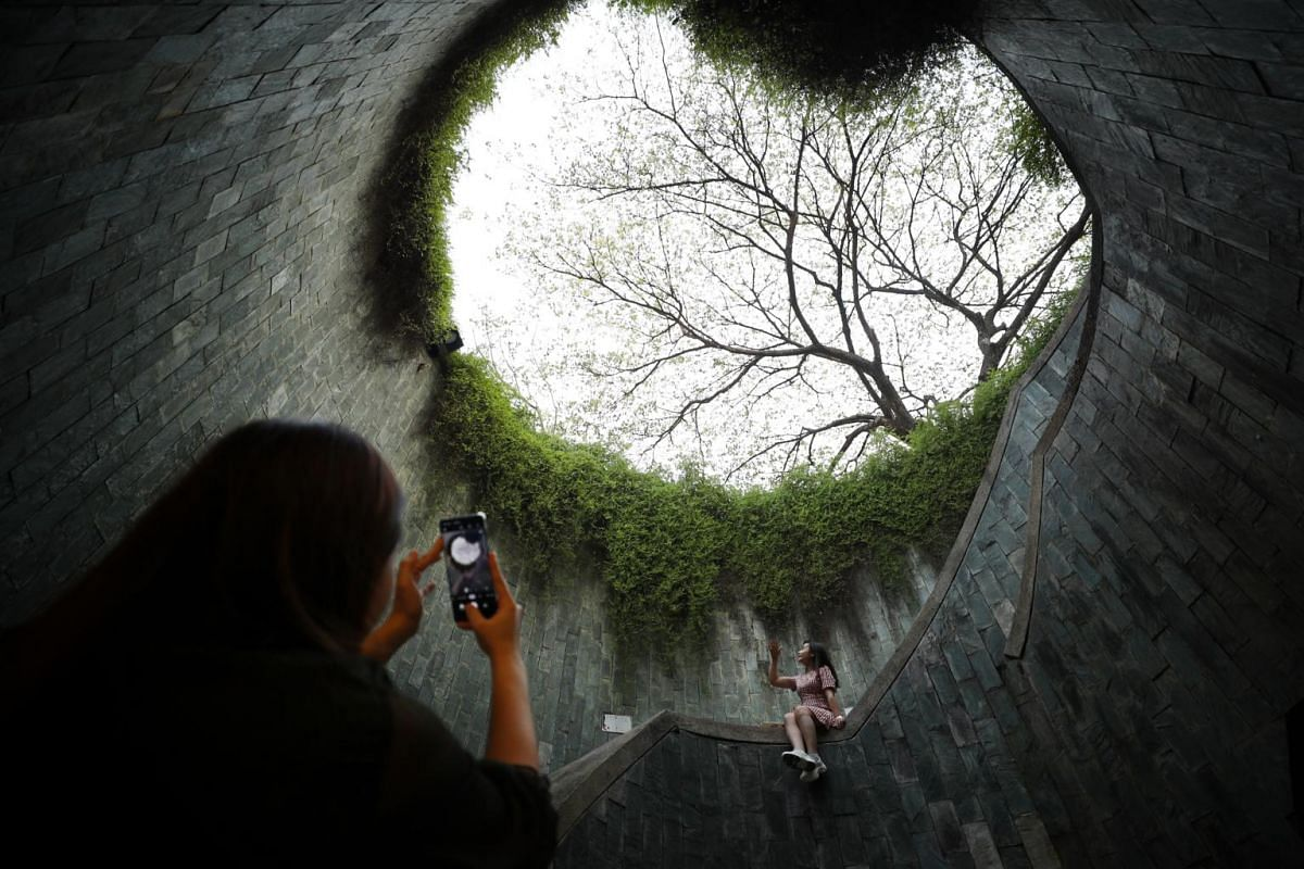 A woman poses for a picture at the spiral staircase at Fort Canning, Singapore, on Dec 1, 2019.