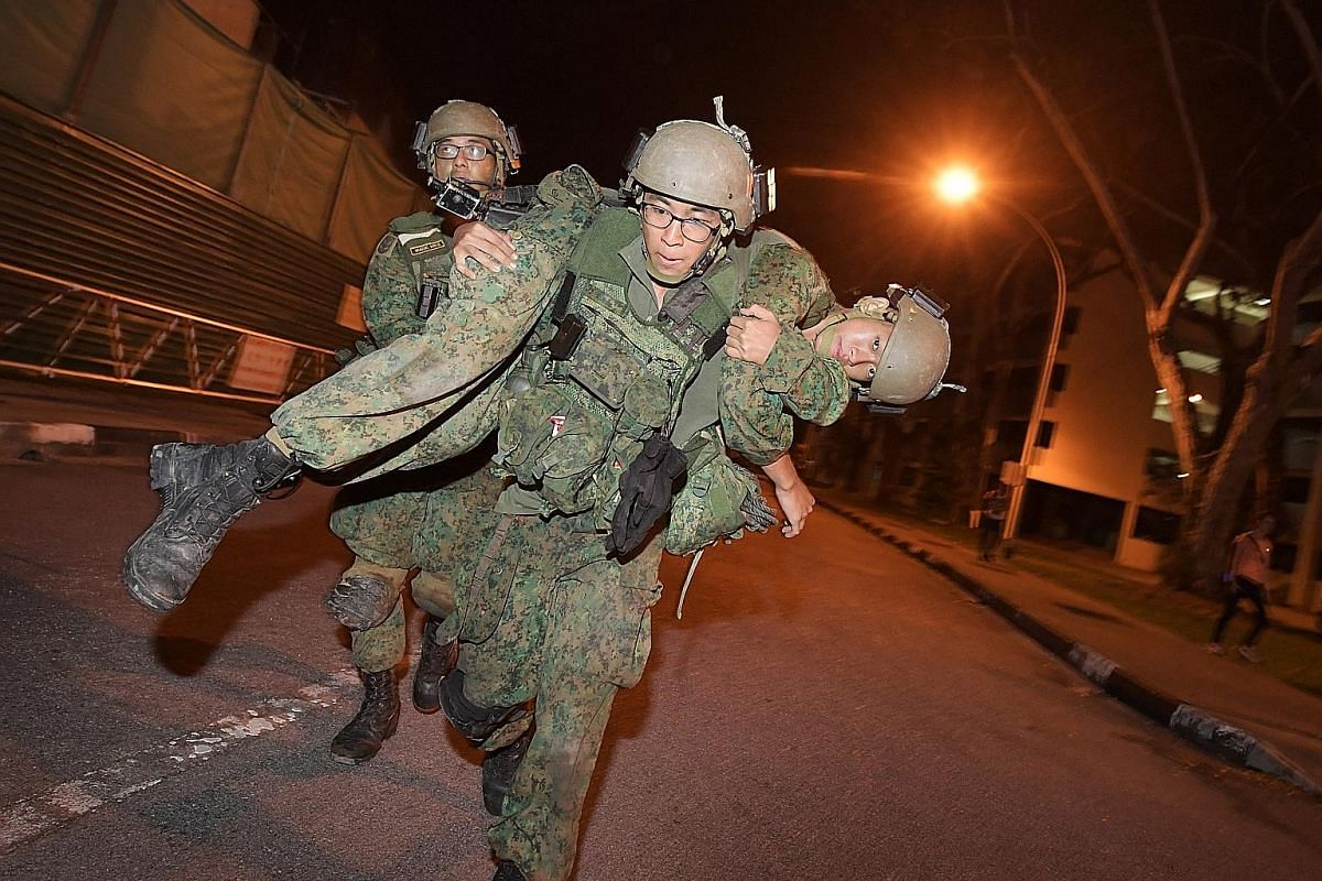 """Above: A """"casualty"""" being evacuated to a safe area following a simulated raid. Below: For the most part, the trainees march on little-used roads away from the public eye, but at times they cross roads such as this one in Loyang Avenue. Below right: W"""