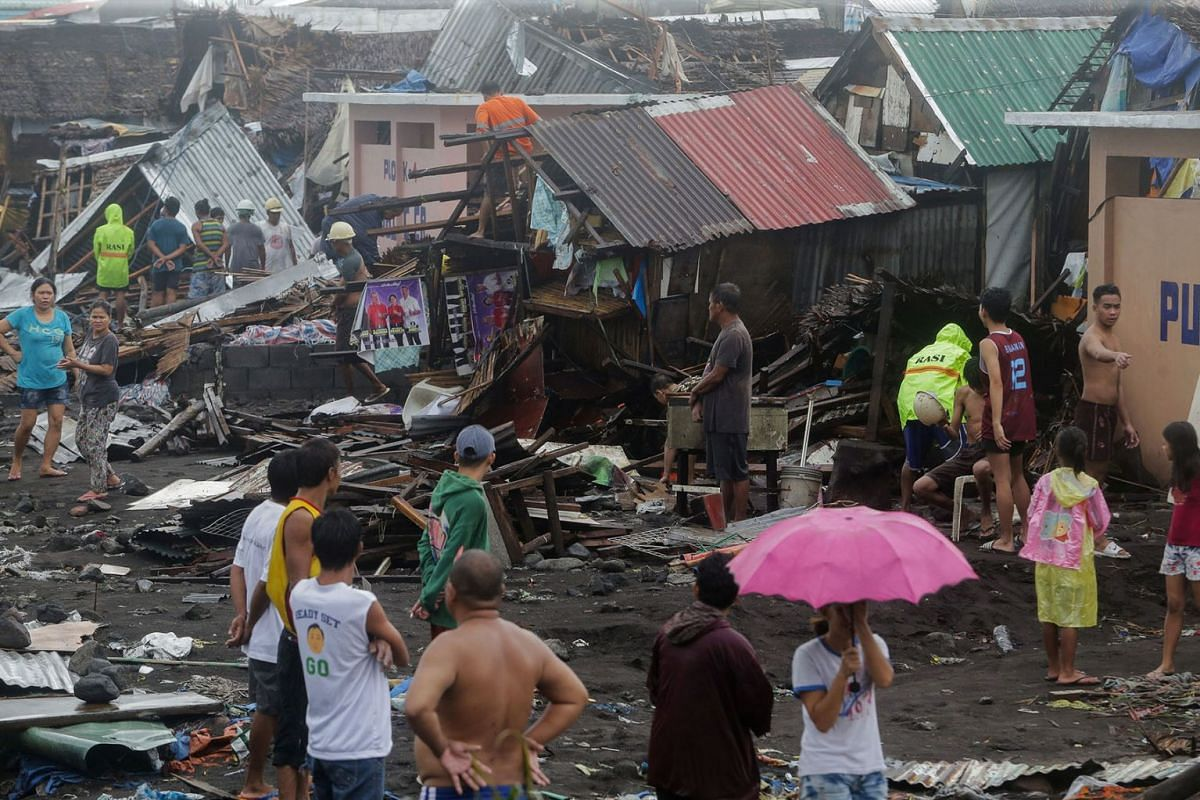 Residents stand among their damaged houses after Typhoon Kammuri hit Legazpi City, Albay, Philippines, December 2, 2019. PHOTO: REUTERS