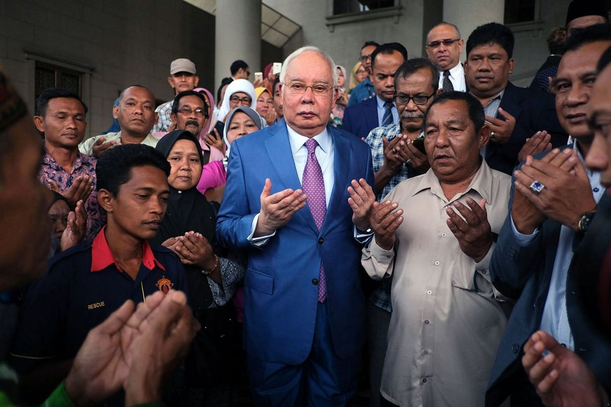 Najib Razak, Malaysia's former prime minister, center, offers prayers with his supporters as he arrives at the Kuala Lumpur Courts Complex in Kuala Lumpur, Malaysia, on Dec. 3, 2019. Najib is set to give his testimony to defend himself against charge