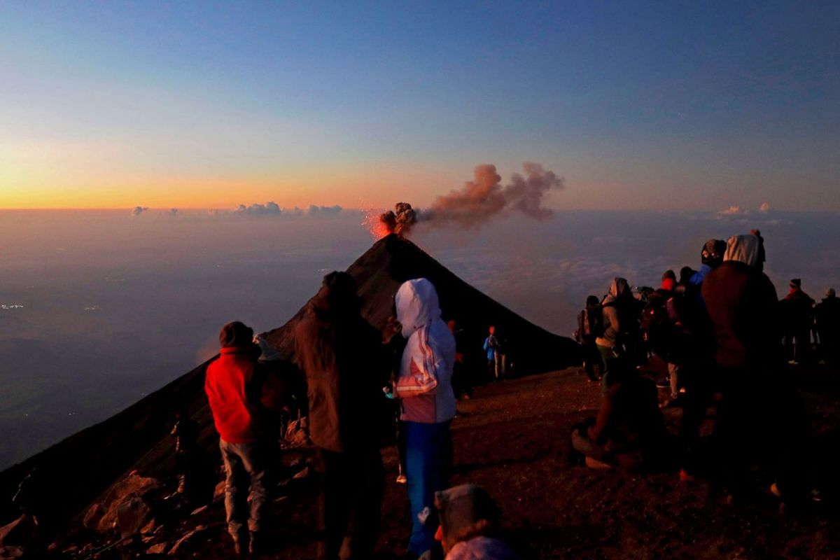 Tourists watch an eruption of Volcan de Fuego, or Chi Q'aq, volcano from atop the Acatenango volcano in Acatenango, Guatemala, December 1, 2019. PHOTO: EPA-EFE