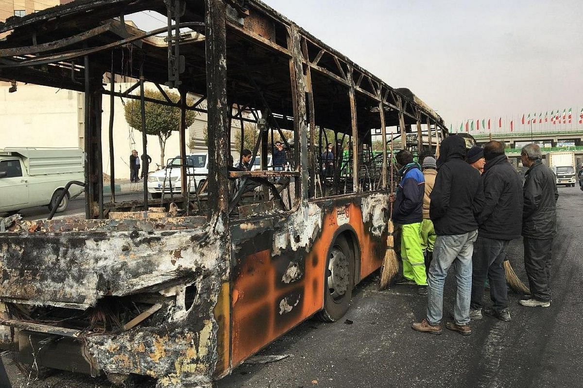 A bank damaged by fire in Teheran after protests on Nov 20. The authorities have arrested dozens and restricted Internet access. Iranians looking at the wreckage of a bus that was set ablaze by protesters during a demonstration in the central city of
