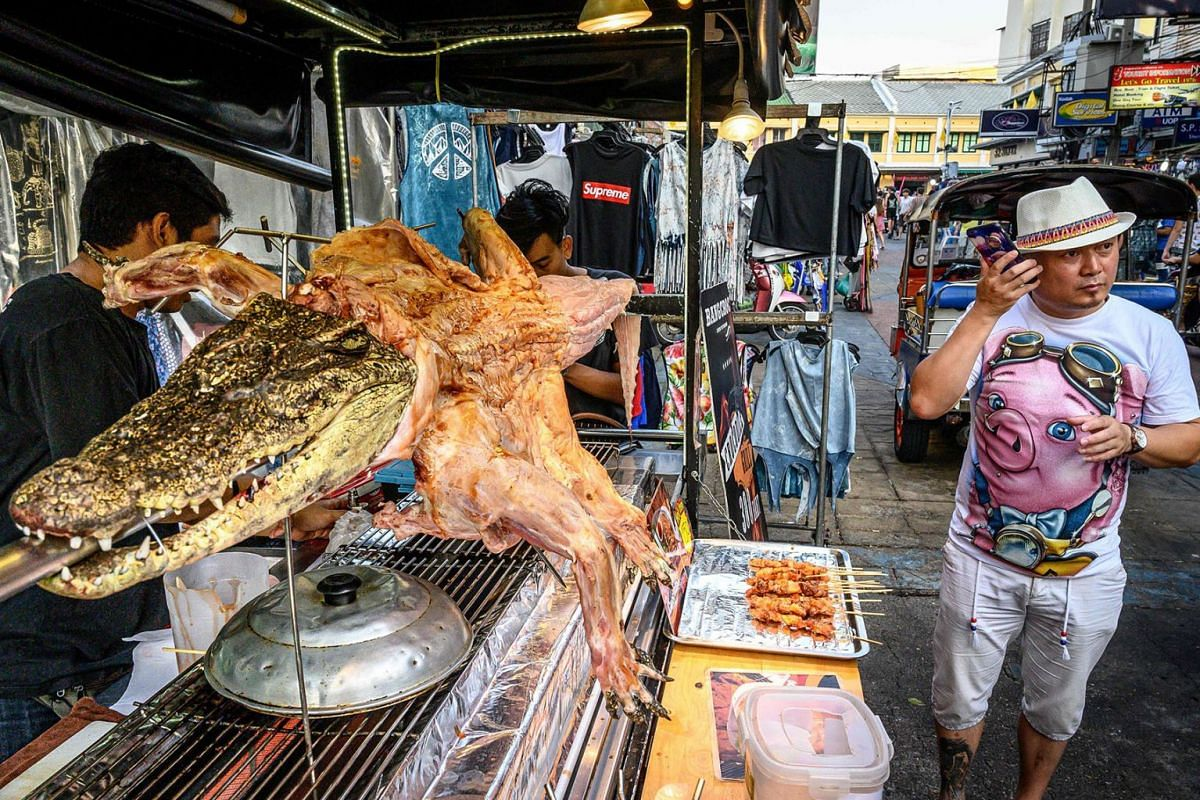 A customer waits to be served roasted crocodile on a street of Bangkok on Dec 3, 2019. PHOTO: AFP
