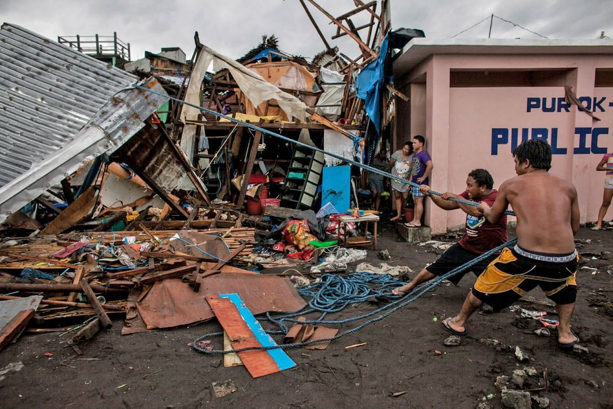 A handout photo made available by Greenpeace-Philippines shows villagers working among damaged houses in the aftermath of Typhoon Kammuri in Legazpi city, Albay Province, Philippines, Dec 3, 2019. PHOTO: HANDOUT VIA EPA-EFE