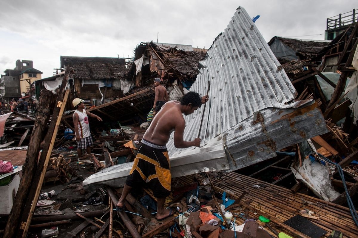 A handout photo made available by Greenpeace-Philippines shows villagers working among damaged houses in the aftermath of Typhoon Kammuri in Legazpi city, Albay Province, Philippines, on  Dec 3, 2019.