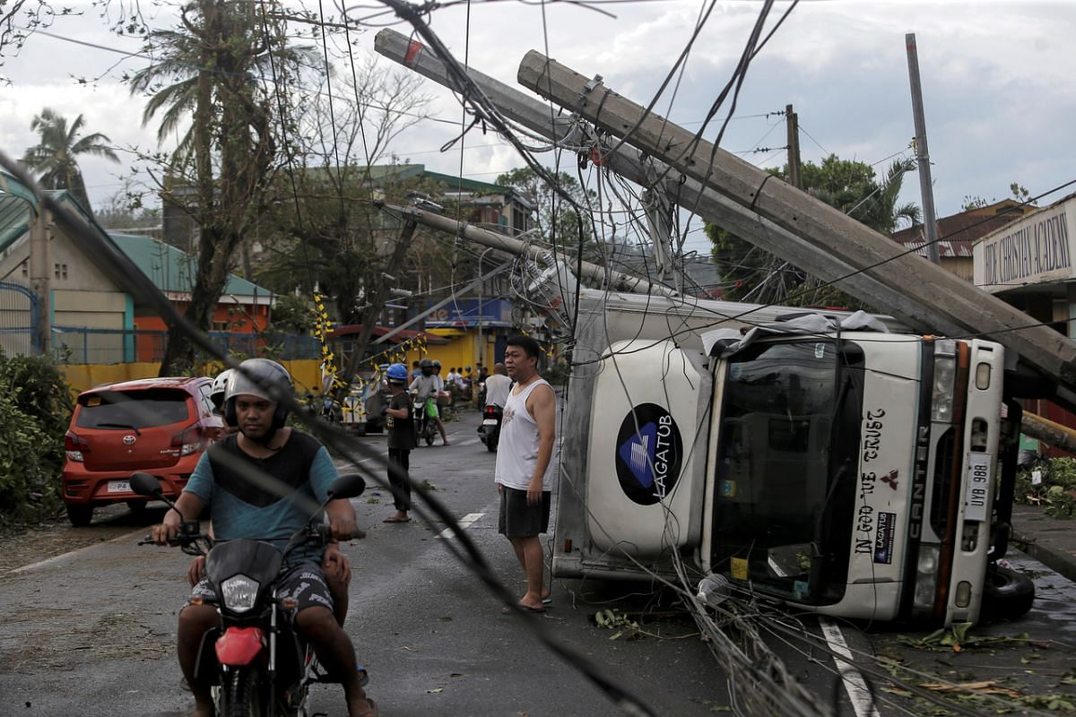 Residents are met by fallen power lines and overturned vehicles after Typhoon Kammuri hit Camalig town, on Dec 3, 2019.