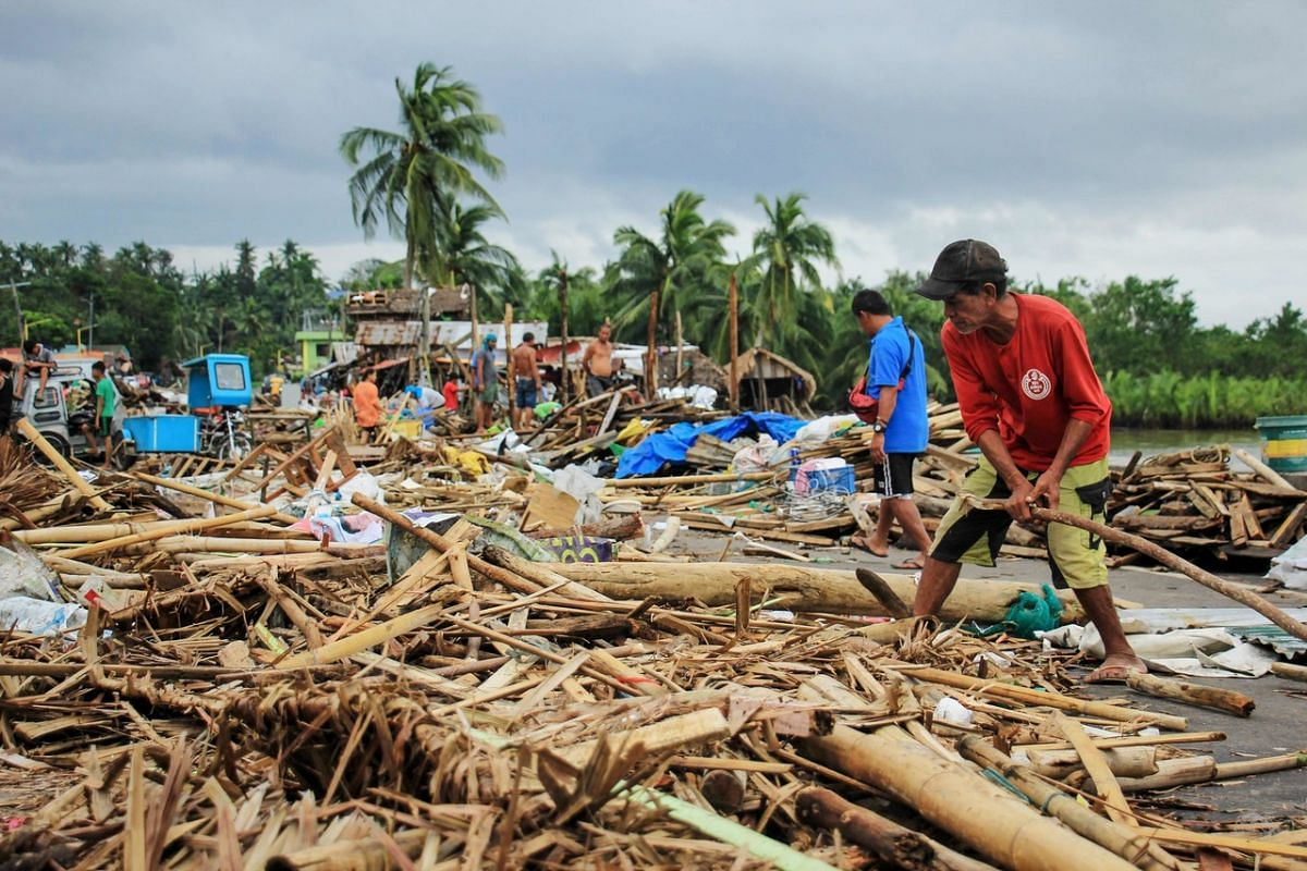 Residents gather debris from their destroyed houses after Typhoon Kammuri hit the city of Sorsogon, south of Manila, on Dec 3, 2019.