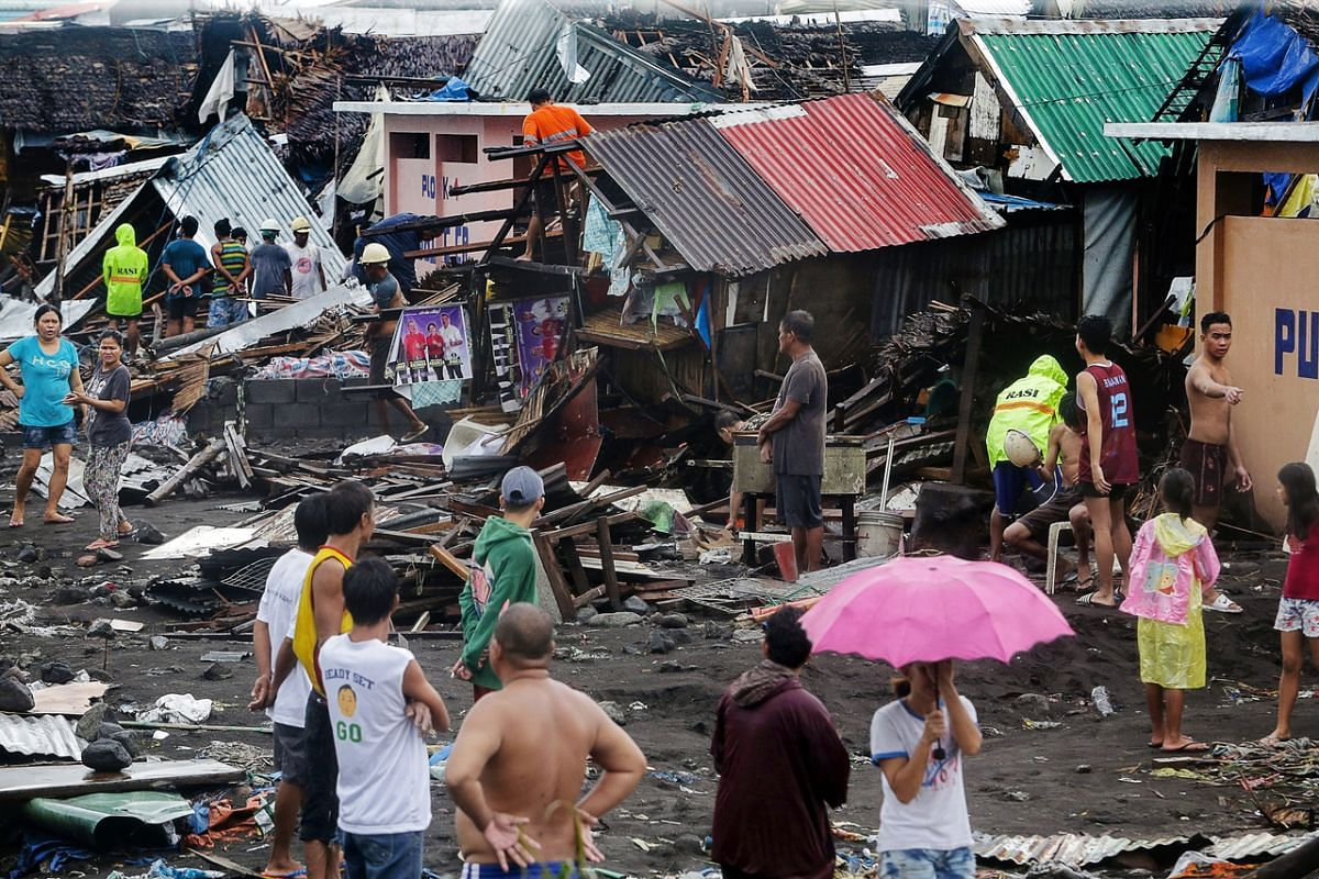 Residents stand among their damaged houses after Typhoon Kammuri hit Legazpi City, Albay, Philippines, on Dec 3, 2019.
