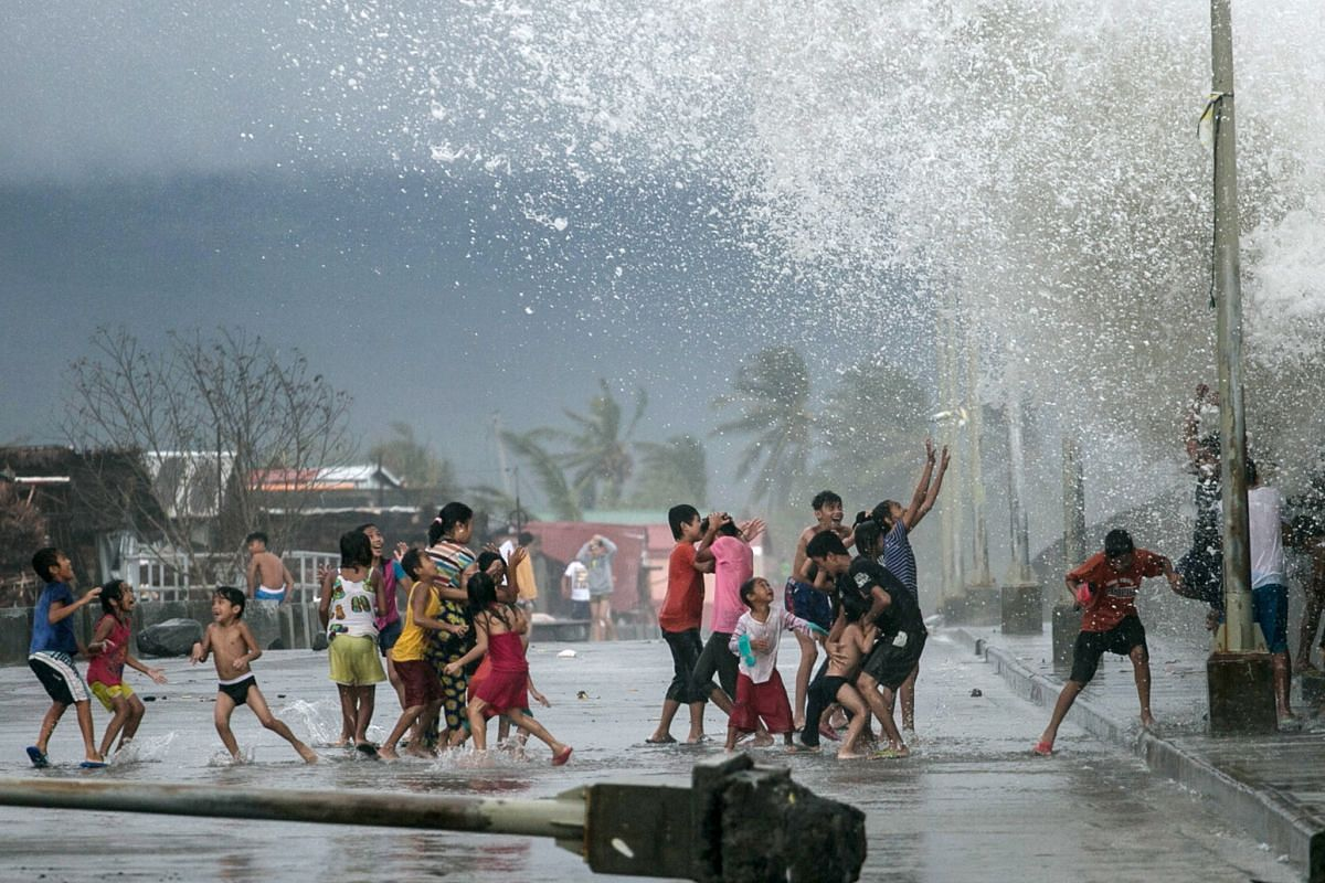 A handout photo made available by Greenpeace-Philippines shows children splashed by strong waves along a dike in the aftermath of Typhoon Kammuri in Legazpi city, Albay Province, Philippines, on Dec 3, 2019.