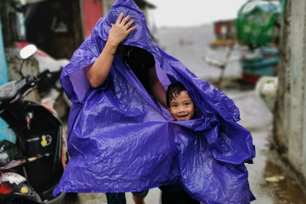 Villagers shelter under a poncho during strong winds brought by Typhoon Kammuri, in Cavite City, Philippines, on Dec 3, 2019.