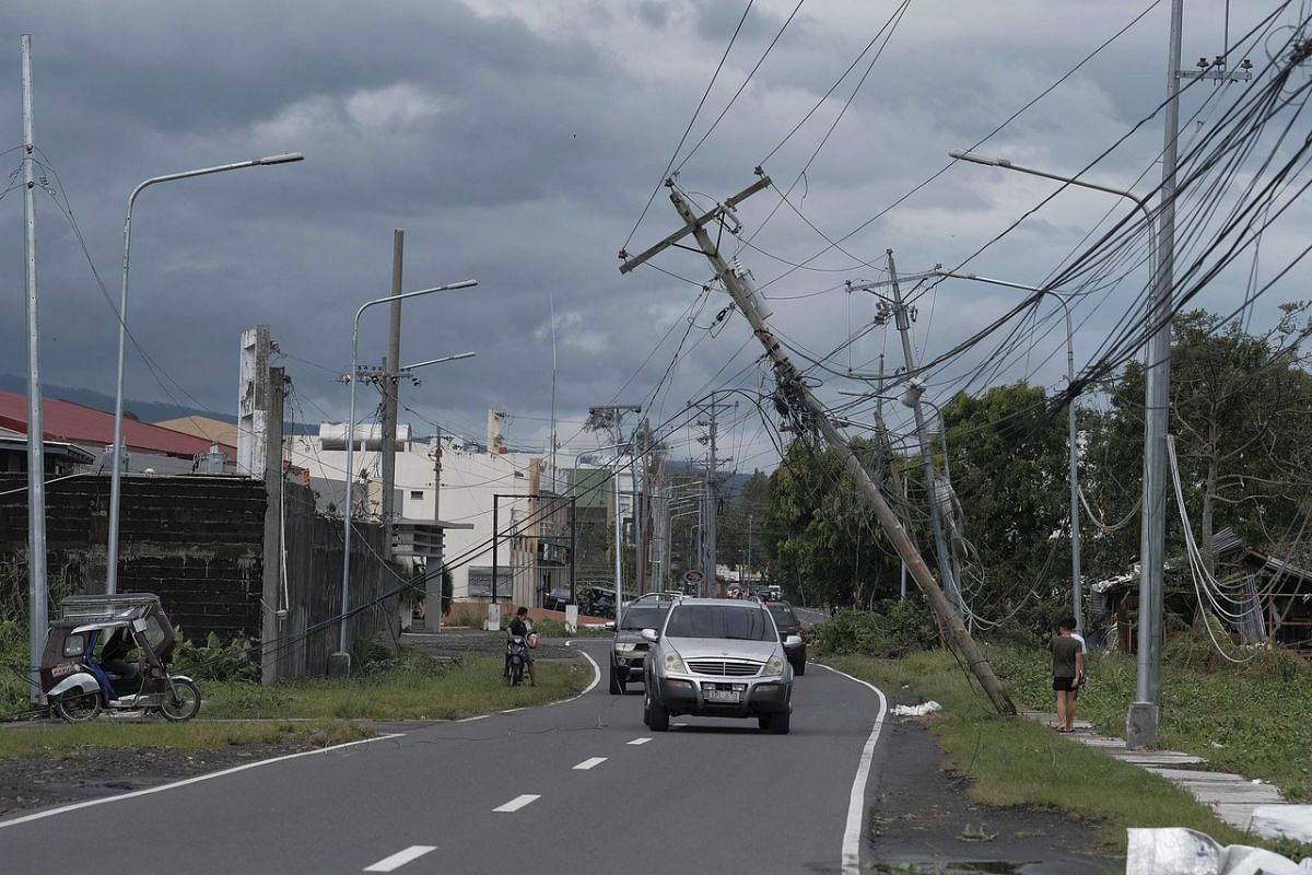 Electrical poles teeter precariously over vehicles after Typhoon Kammuri slammed Legazpi city, Albay province, south-east of Manila, Philippines, on Dec 3, 2019.