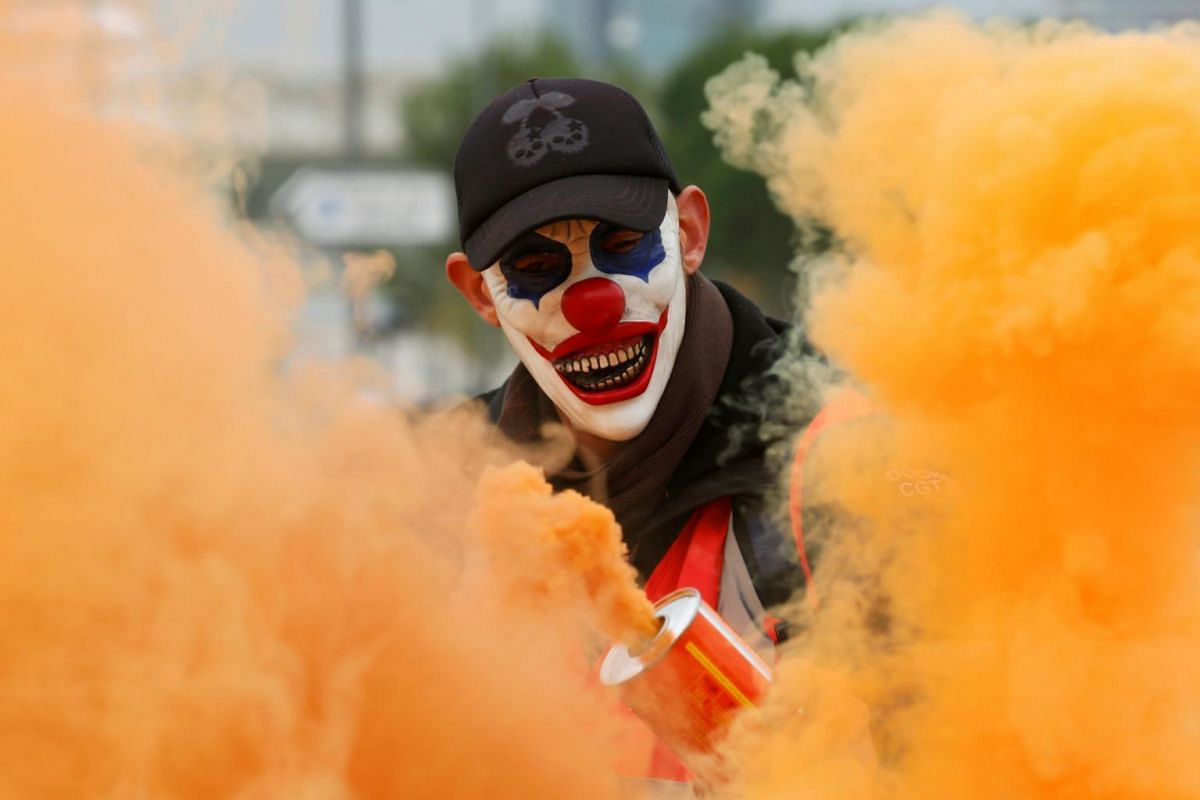 A protester wearing a mask is seen in the smoke as French labour union members demonstrate against the government's pension reform plans in Marseille, as part of a day of national strikes and protests in France, on Dec 5, 2019.