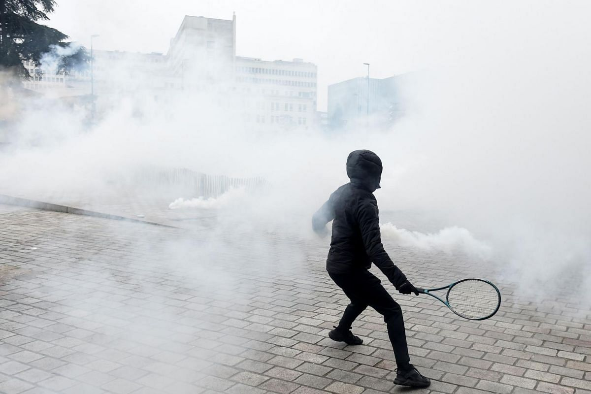 A protester engulfed in tear gas uses a tennis racket to throw back a tear gas canister to the anti-riot police during a demonstration against the pension overhauls in Nantes, on Dec 5, 2019.