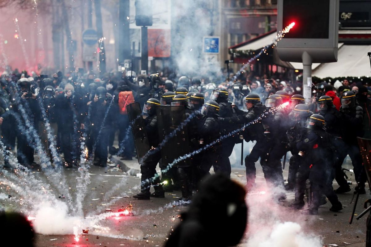 French riot police clash with protesters during a demonstration against pension reforms in Paris, France, on Dec 5, 2019.