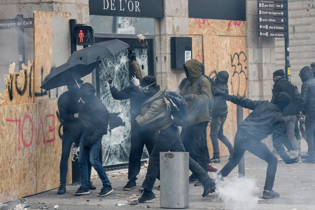 Protesters hurl stones next to a broken shop window during a demonstration against the pension overhauls in Nantes, on Dec 5, 2019.