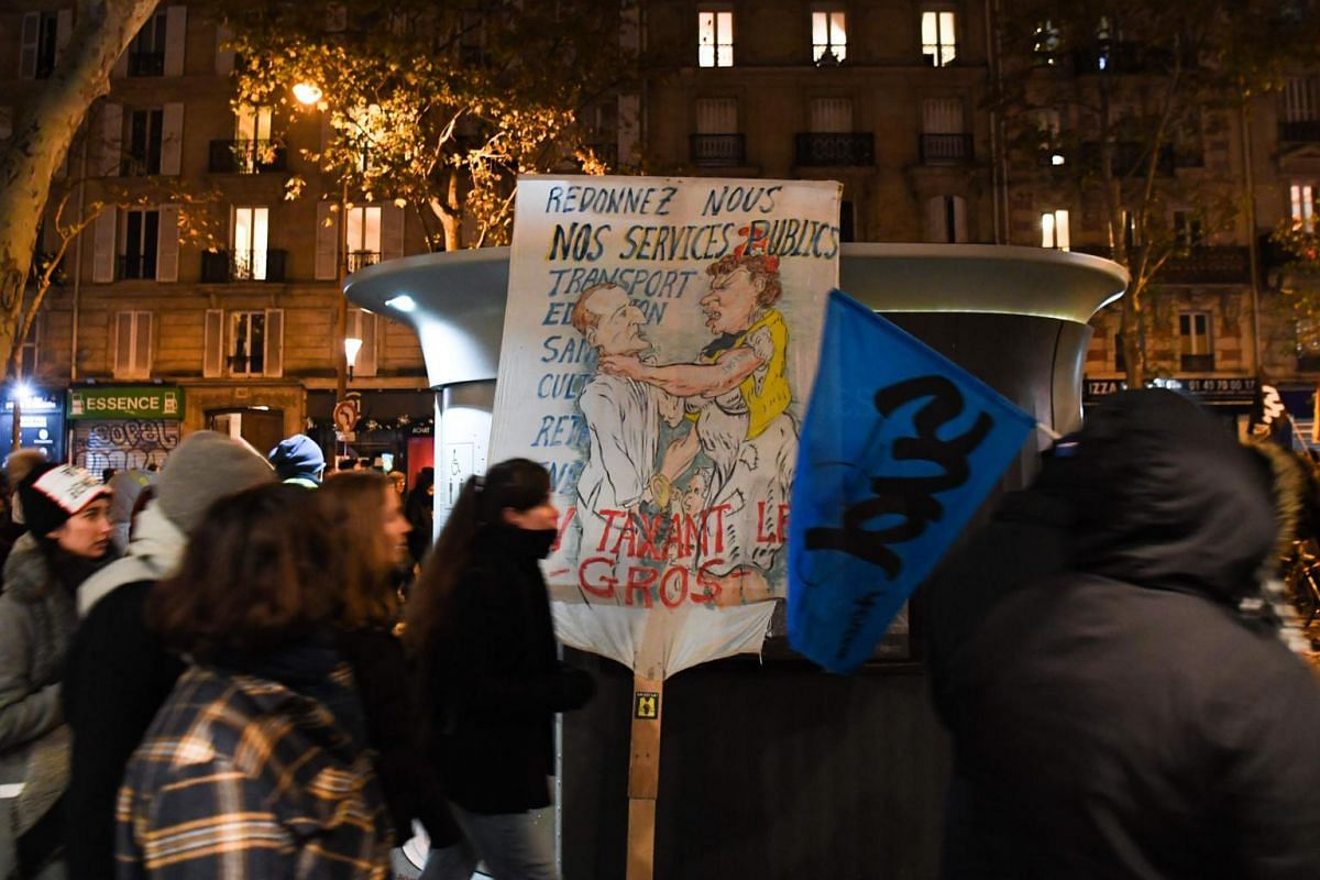 """Protesters walk past a placard depicting President Emmanuel Macron being strangled by a """"yellow vest"""" protester and reading in French """"Give us back our public services"""" during a demonstration against the pension overhauls in Paris, on Dec 5, 2019."""