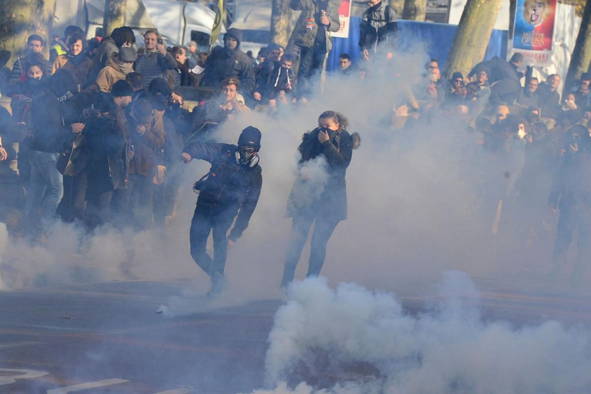 A man throws a tear canister back as people stand amid tear gas smoke during a demonstration against the pension overhauls in Bordeaux, on Dec 5, 2019.