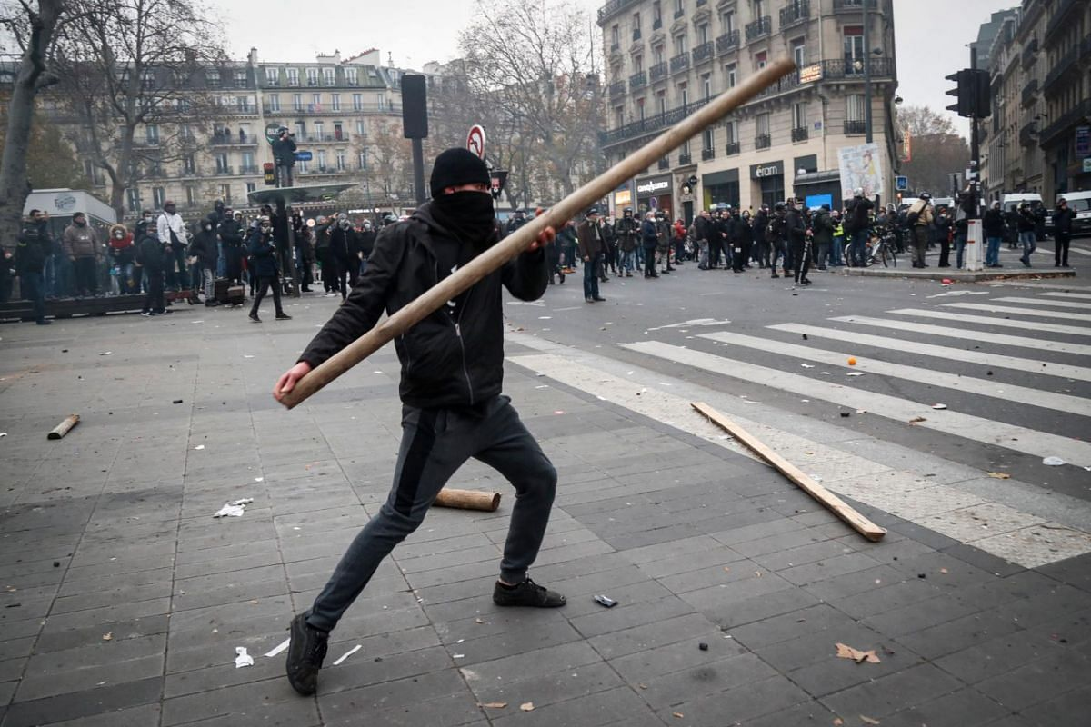 A protester throws a piece of wood during a demonstration to protest against the pension overhauls, at the Place de la Republique in Paris, on Dec 5, 2019.