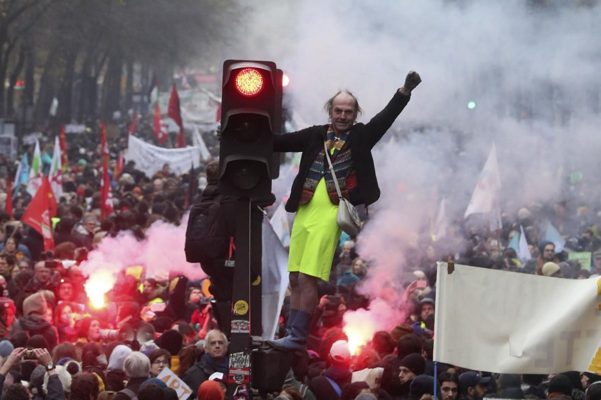 A man stands on a traffic light during a demonstration in Paris, on Dec 5, 2019.